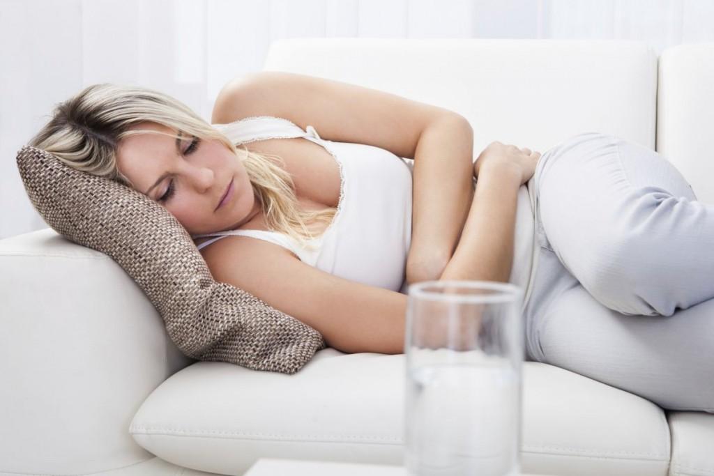 женщина лежит и держится за живот