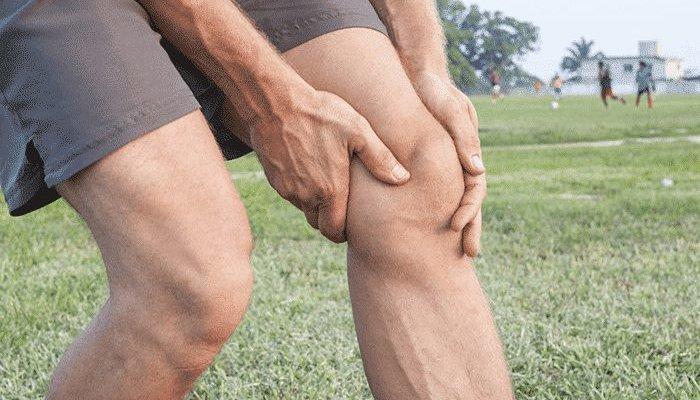 мужчина держится за колено