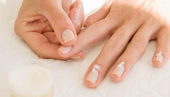 женщина мажет крем на ногти